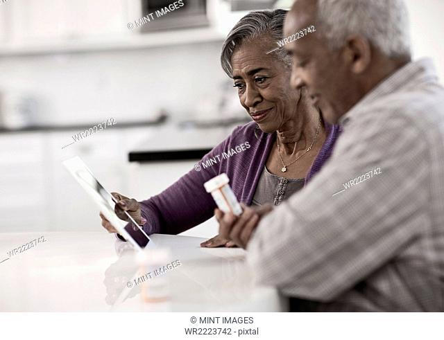 A grey haired couple sitting at a table, looking at information on a digital tablet