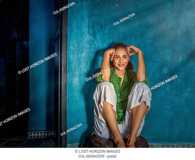 Woman sitting on pouffe looking at camera smiling, Marrakesh, Morocco