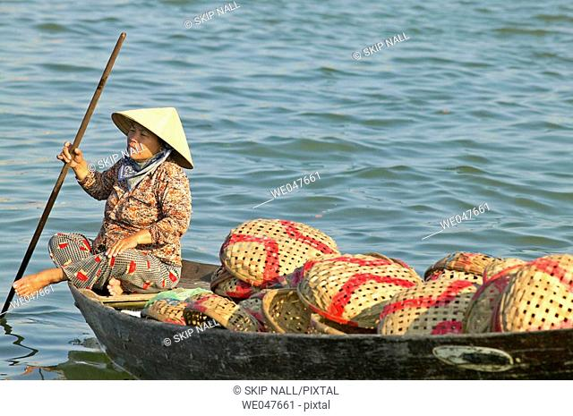Woman in boat near fish market in Hoi An, Vietnam