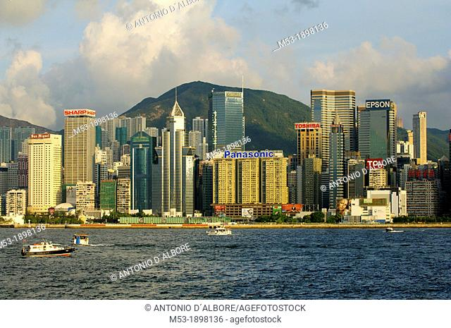 Commercial buildings in Admirality and Wanchai on Hong Kong island at sunset  In foregrounds the waters of Victoria Habor  Hong Kong  China
