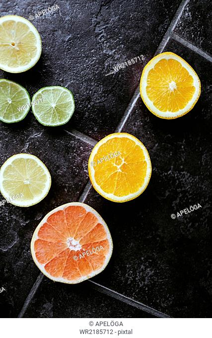 Directly above shot of sliced citrus fruits on tiled floor