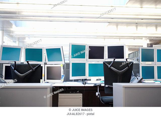 Empty computer workstations with many monitors