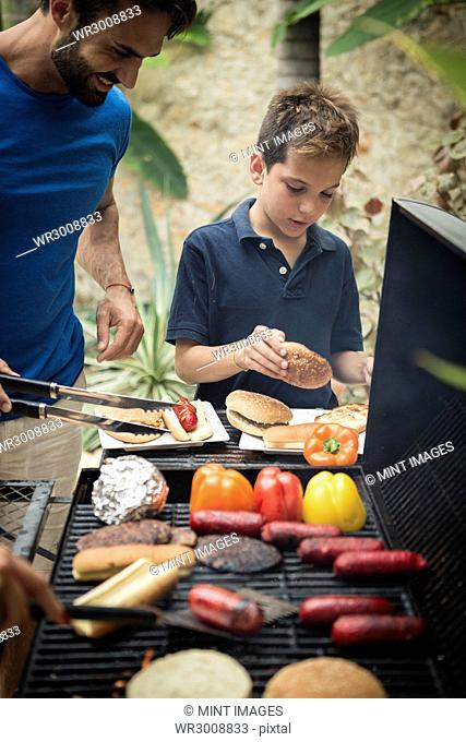 A man and boy standing at a barbecue cooking food