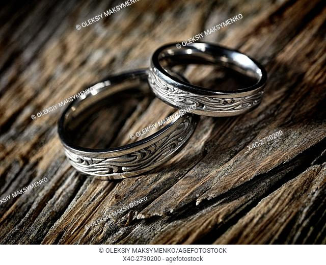 Two white gold wedding rings with Celtic design on rustic wood background, artistic still life