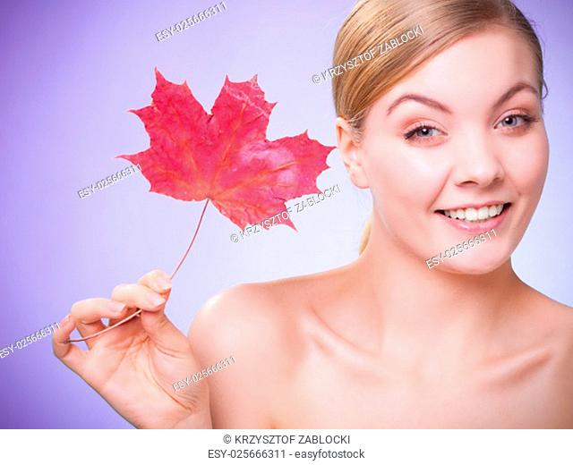 skincare habits. portrait of young woman with leaf as a symbol of red capillary skin on violet. face of girl taking care of her dry complexion