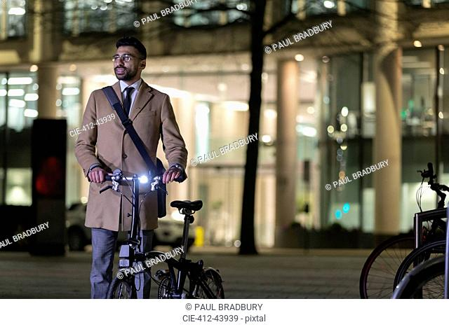 Businessman with bicycle on urban street at night