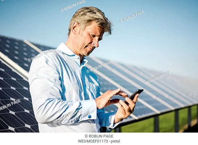 Businessman using smartphone at solar park