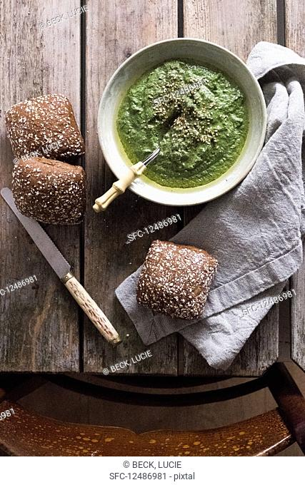 Spinach pesto in a bowl with bread at a wooden table and a chair