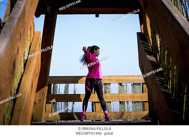 Woman stretching on wooden bridge