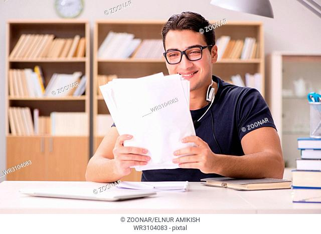 Happy male student preparing for his exams