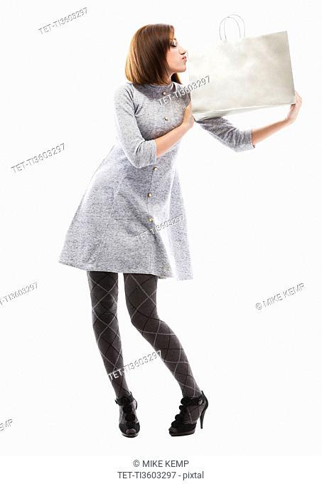 Young woman holding shopping bag, studio shot