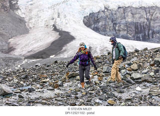 A husband and wife hike on the rugged surface of Gulkana Glacier; Alaska, United States of America