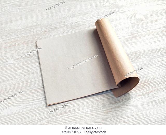 Bank square brochure or magazine on light wooden background. Responsive design mockup