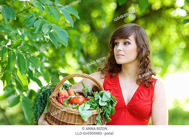 Young woman holding basket filled vegetables, Debica, Poland