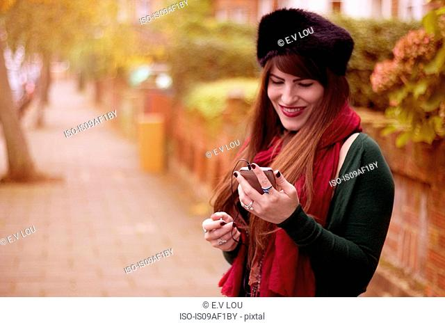 Young woman wearing winter clothing, holding smartphone