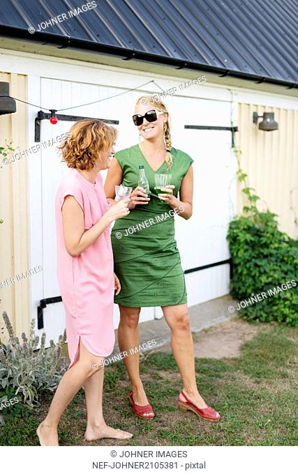 Two young women drinking cocktails in back yard