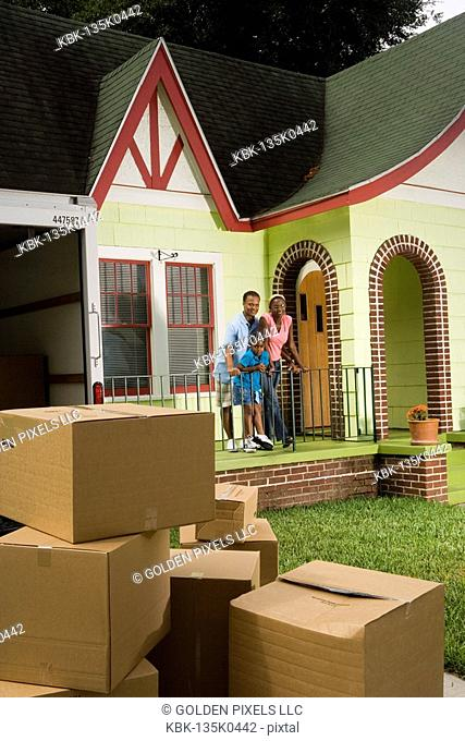 Family standing outside house, with moving boxes piled in driveway