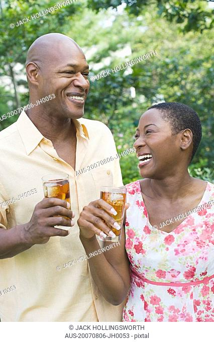 Close-up of a couple holding glasses of ice tea and smiling