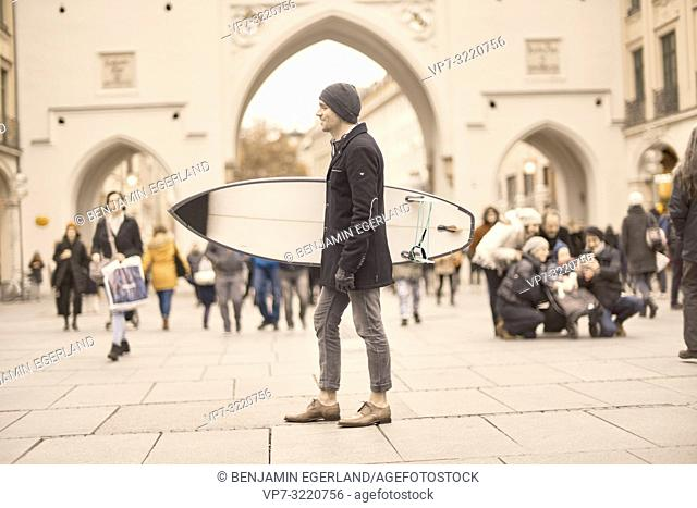 man with surfboard in city, longing for holiday, in Munich, Germany