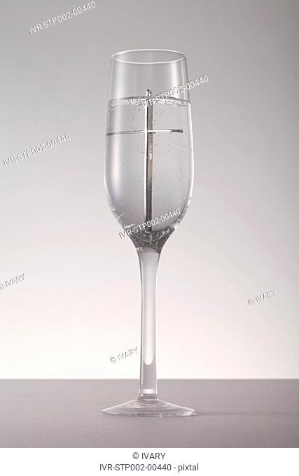 Cross inside of champagne glass against gray background