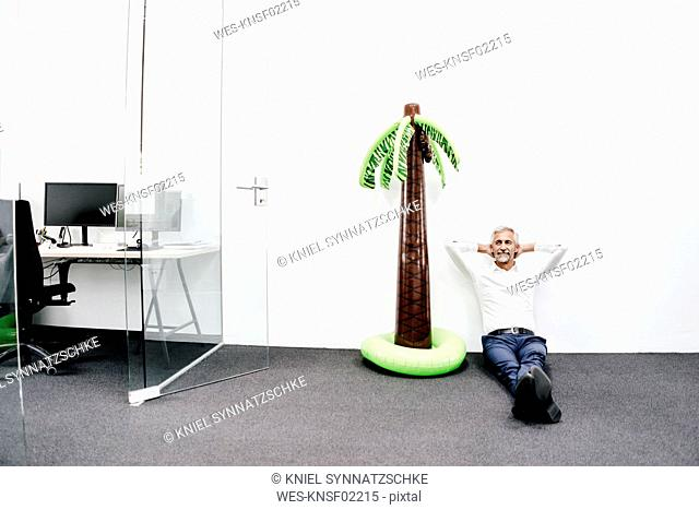 Smiling mature businessman sitting next to inflatable palm tree in office