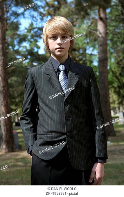 A Teenage Boy Standing In A Cemetery; Edmonton, Alberta, Canada