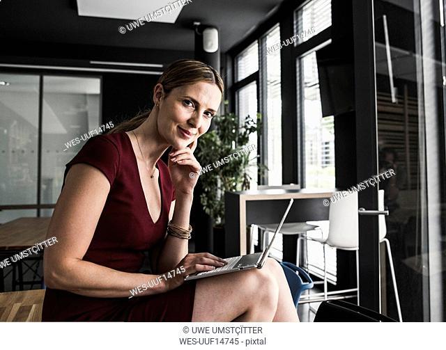Businesswoman in office wearing burgundy dress using laptop