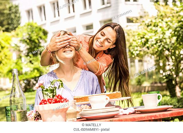Two female friends in garden, one coverings the others eyes with hands