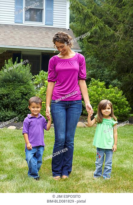Mother holding hands with son and daughter in front yard