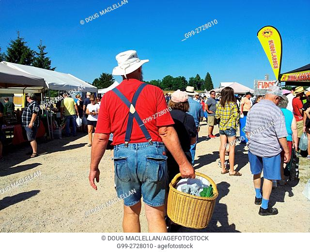 A man in a white hat, suspenders, red shirt and blue shorts walks with a basket with a crowd of people at a weekly rural market on a farm in Ontario, Canada