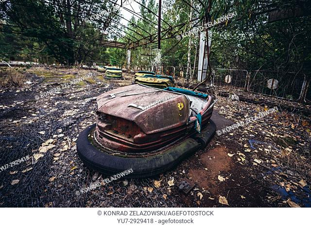 Red bumper car in amusement park of Pripyat ghost city, Chernobyl Nuclear Power Plant Zone of Alienation around nuclear reactor disaster in Ukraine