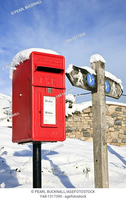 Red Wharf Bay, Isle of Anglesey, North Wales, UK, Europe  Red postbox and coastal path signpost in the snow