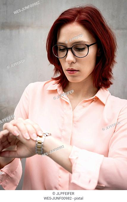 Portrait of a young businesswoman looking on her wristwatch