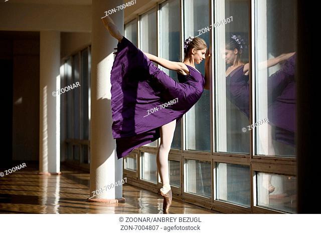 Graceful ballerina dancing in a purple dress leg lifted high, st