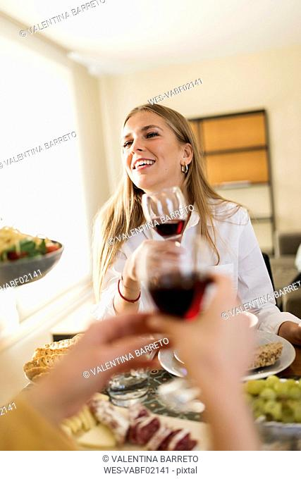 Young woman drinking red wine ata lunch with friends