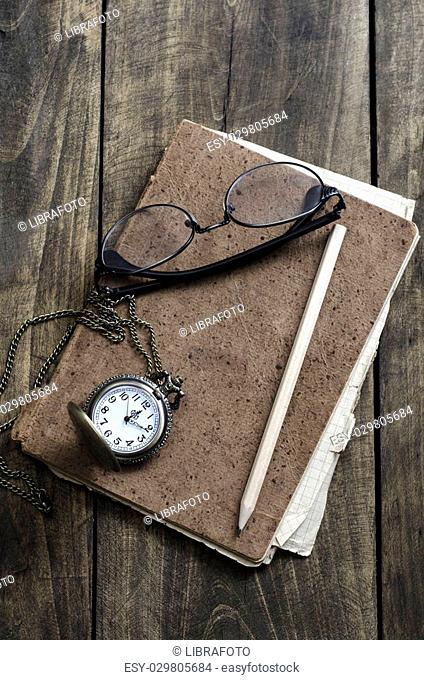 Pocket watch, glasses and old notebook on table, close up