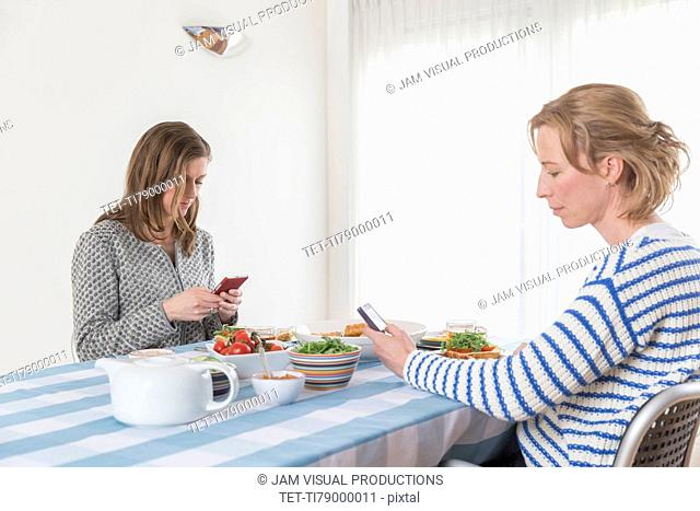 Women checking phones at laid table in dining room