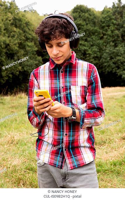 Teenage boy, standing in fields, wearing headphones, using smartphone