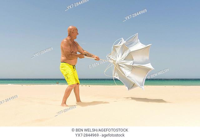 Man with sun umbrella on a windy day. Tarifa, Costa de la Luz, Cadiz, Andalusia, Spain