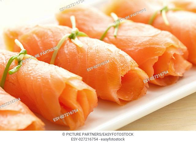 Rolls of smoked salmon with chives as a snack