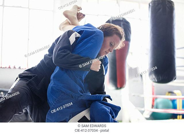 Determined woman practicing judo, tackling in gym