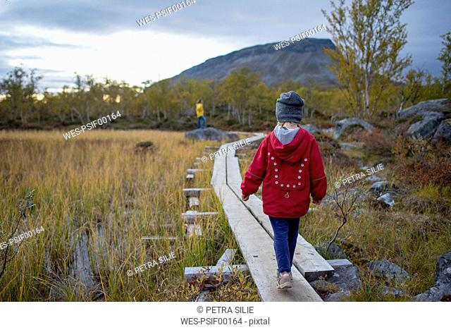 Finland, Lappland, Kilpisjaervi, girl on boardwalk, rear view