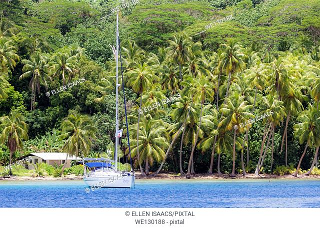 Tropical scene of sailboat anchored in front of palm trees and house in French Polynesia