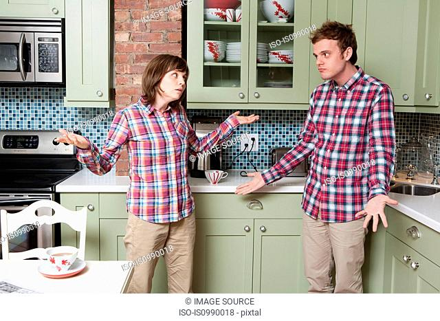 Young couple shrugging in kitchen