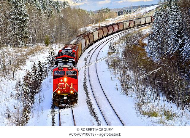 A Canadian National freight train traveling a curve after a fresh snowfall in rural Alberta, Canada