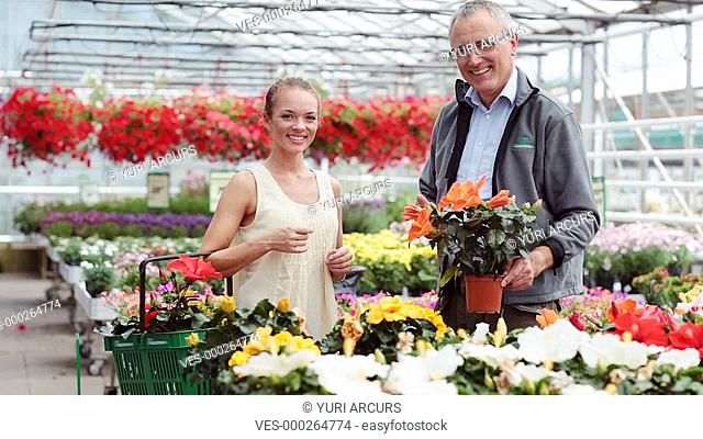 Pretty woman and a friendly man smiling at the camera in a plant nursery full of colourful plants and flowers