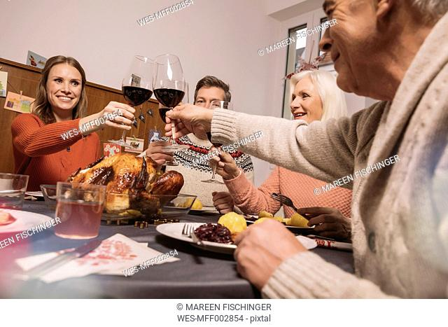 Family clinking glasses during Christmas dinner