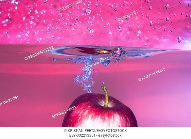 Red apple splashing into water with red background, lovely soft colour  Many drops and wet photografer after that serie :-