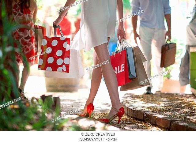 Waist down view of young woman strolling busy city street carrying shopping bags