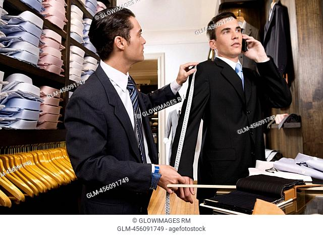 Tailor taking the measurements of a customer